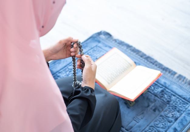 Muzułmanka modli się koralikami i czyta koran
