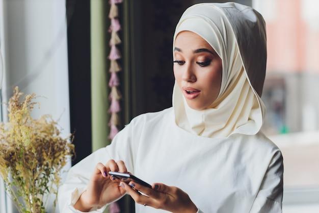 Muzułmanka rozmawia przez telefon komórkowy w kawiarni