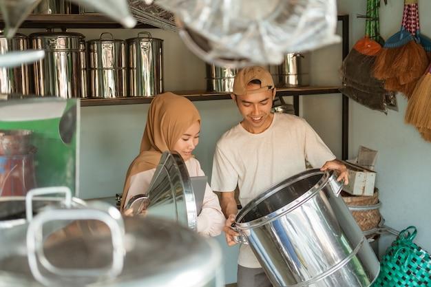 Muzułmanka stoi przy użyciu tabletu po otwarciu przykryj dużą patelnię z mężczyzną trzymającym dużą patelnię w sklepie agd