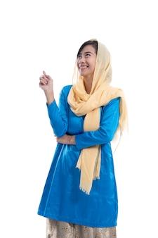 Muzułmanka ubrana na niebiesko patrzy w górę i myśli, aby skopiować przestrzeń