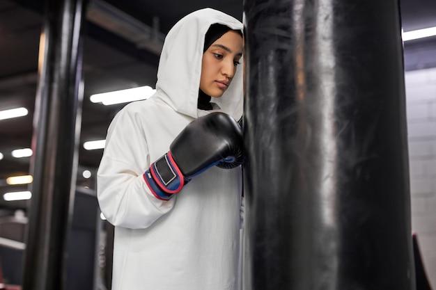 Muzułmanka uderzająca w worek treningowy, silna arabka ćwicząca samotnie w centrum fitness, ubrana w hidżab. sport, fitness, koncepcja boksu