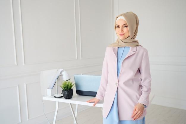 Muzułmanka w beżowym hidżabie i tradycyjnych strojach stojąca w pobliżu miejsca pracy
