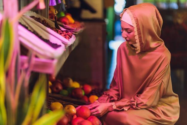 Muzułmanka w hidżabie kupująca artykuły spożywcze w supermarkecie w centrum handlowym.