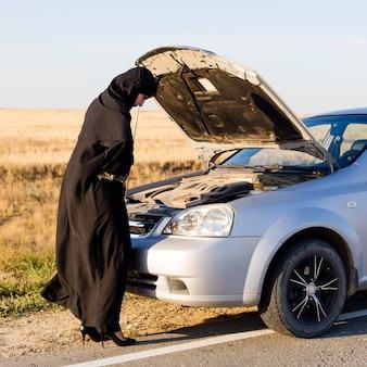 Muzułmanka w pobliżu otwartej maski samochodu na pustej drodze