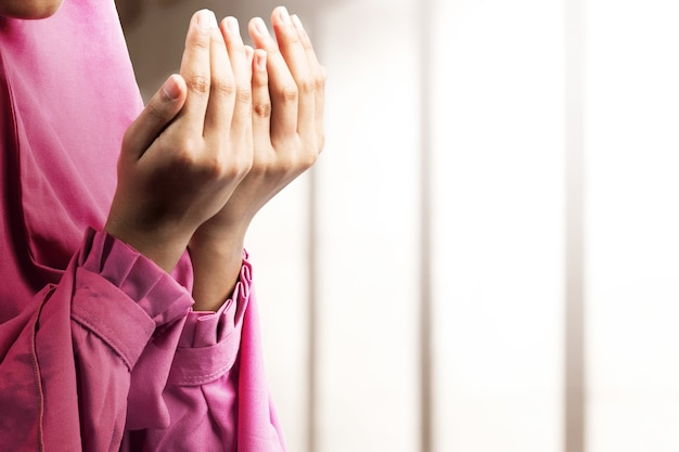Muzułmanka w welonie stojąc z podniesionymi rękami i modląc się na meczecie