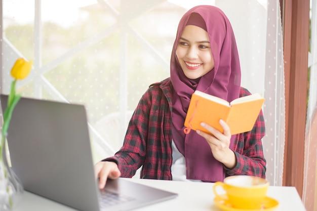 Muzułmanka z hidżabem pracuje z laptopem w kawiarni