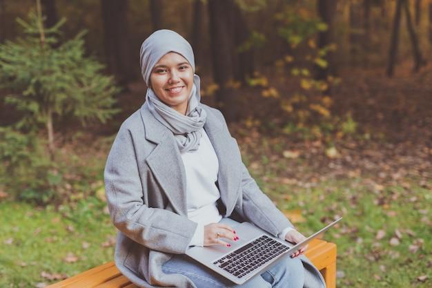 Muzułmanka z laptopem w parku.