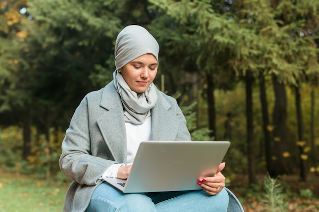 Muzułmanka z laptopem w parku