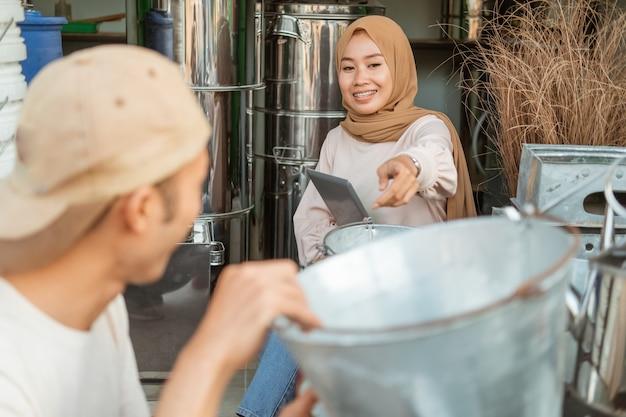 Muzułmanka za pomocą tabletu z palcem wskazującym do wyboru wiadra z asystentem w sklepie agd