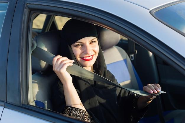 Muzułmanka zapinanie pasów bezpieczeństwa w samochodzie. odzież tradycyjna.
