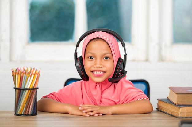 Muzułmanki uczące się online w domu aby zmniejszyć dystans społeczny i zapobiec chorobom zakaźnym