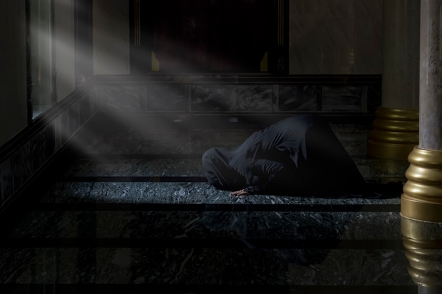 Muzułmanki w czarnych koszulach. robienie modlitwy zgodnie z zasadami islamu.