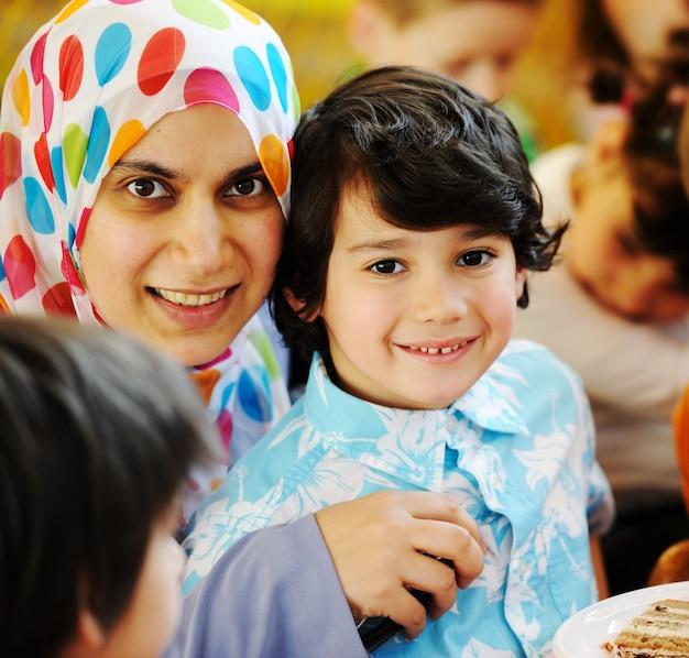 Muzułmańska arabska matka z dziećmi bawić się przy przyjęciem urodzinowym