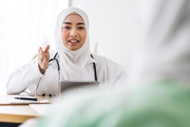 Muzułmańska azjatycka kobieta konsultuje się z lekarzem i sprawdza informacje z muzułmanką