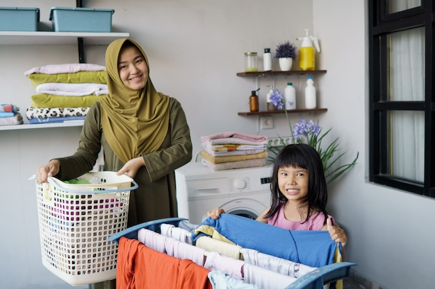 Muzułmańska azjatycka matka i dziecko dziewczynka mały pomocnik w pralni w pobliżu pralki