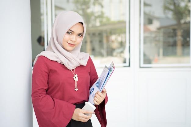 Muzułmańska biznesowa kobieta trzyma telefon komórkowego i raport.