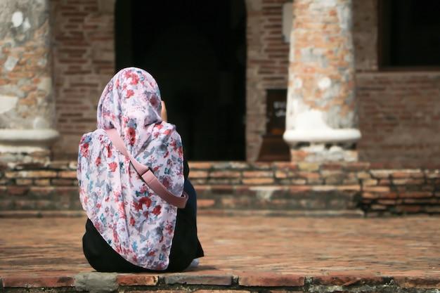 Muzułmańska dziewczyna nosi hidżab i siedzi przed starożytną architekturą.