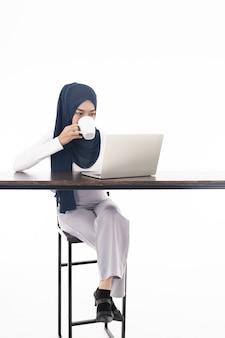 Muzułmańska dziewczyna używa laptop kawę