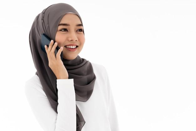 Muzułmańska dziewczyna używa telefon komórkowego