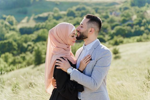 Muzułmańska historia miłosna mieszanej pary. mężczyzna i kobieta uśmiechają się i przytulają na zielonych wzgórzach