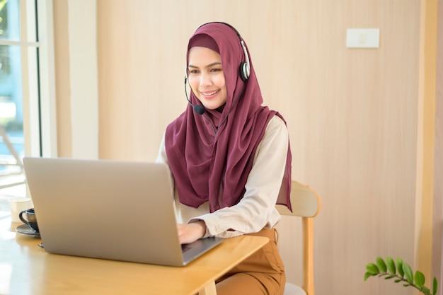 Muzułmańska kobieta operatora w zestawie słuchawkowym za pomocą komputera, odpowiadając na wezwanie klienta w biurze, koncepcja obsługi klienta