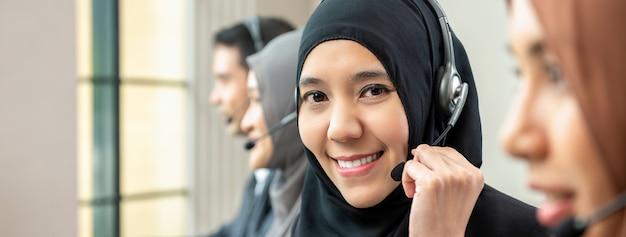 Muzułmańska kobieta pracuje jako obsługa klienta operator z drużyną w centrum telefonicznym