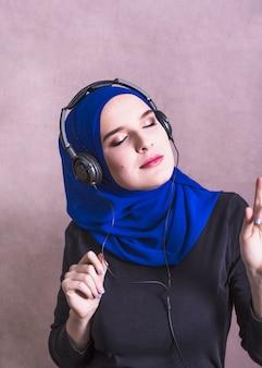 Muzułmańska kobieta słucha muzyka na hełmofonach