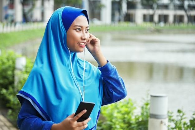 Muzułmańska kobieta słucha muzyka na ulicie