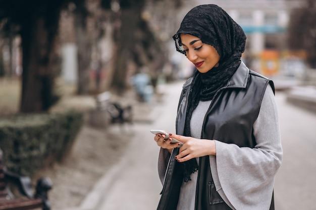 Muzułmańska kobieta używa telefon na zewnątrz w ulicie