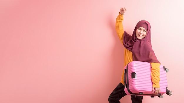 Muzułmańska kobieta z hijab trzyma bagaż na różowym tle, ludzie podróżuje pojęcie