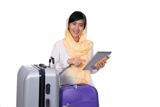 Muzułmańska kobieta z pastylki walizką i paszport nad bielem