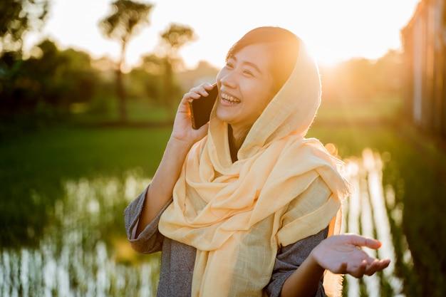 Muzułmańska kobieta z smartphone plenerowym