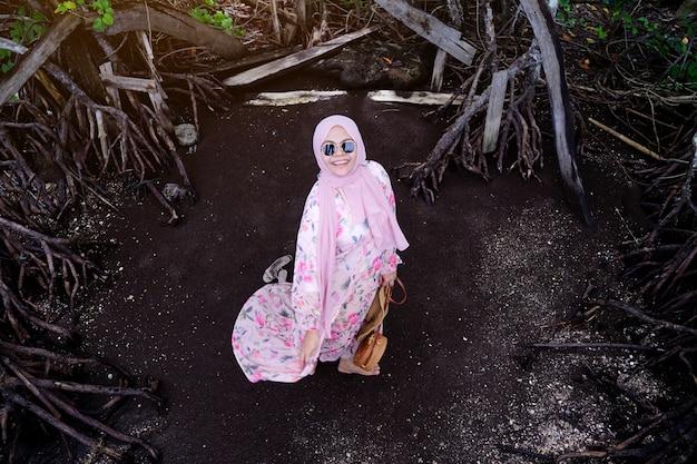 Muzułmańska kobiety pozycja na czarnej piasek plaży w wakacje, azjatycki turystyczny odprowadzenie na ciemnym tle.