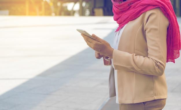 Muzułmańska kobiety przesyłanie wiadomości na telefonie komórkowym w mieście
