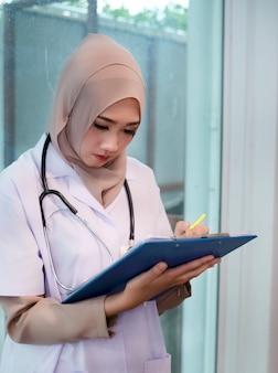 Muzułmańska lekarka pisze na karcie pacjenta, pracując w szpitalu, z poważnym uczuciem