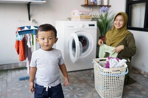 Muzułmańska matka gospodyni domowa z dzieckiem zajmująca się praniem z pralką