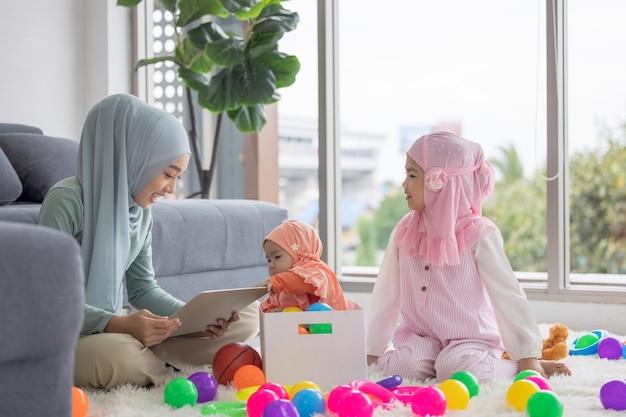 Muzułmańska matka pracuje z laptopem i słodkie małe dziecko bawi się zabawkami w salonie w domu.