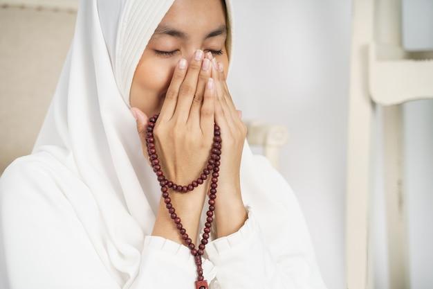 Muzułmańska młoda kobieta modli się w białych tradycyjnych ubraniach