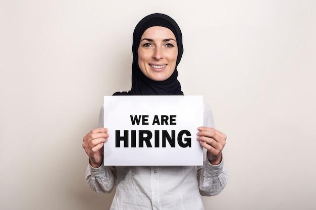 Muzułmańska młoda kobieta w hidżabie trzyma sztandar z tekstem zatrudniamy