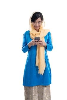 Muzułmańska młoda kobieta za pomocą telefonu komórkowego na białym tle
