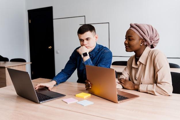 Muzułmańska murzynka i biały mężczyzna z laptopem. wieloetniczna para pracuje razem online nad projektem biznesowym.