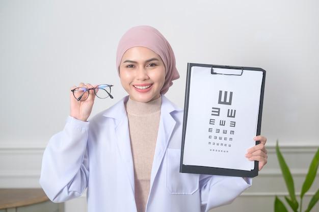Muzułmańska okulista trzymająca test karty wzroku do pomiaru ostrości wzroku