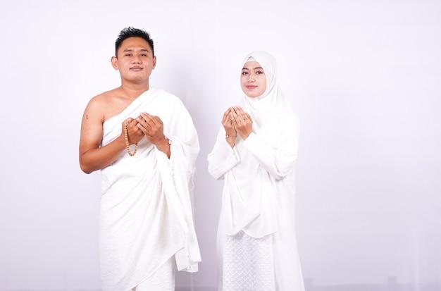 Muzułmańska para modli się na białym tle
