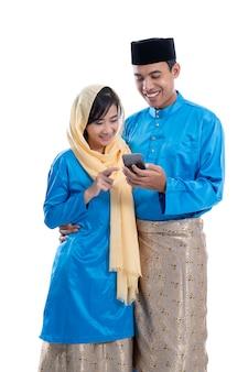 Muzułmańska para używa telefon komórkowego