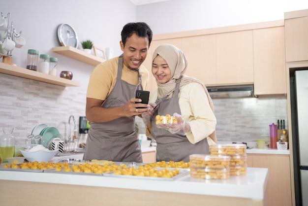Muzułmańska para używa telefonu komórkowego do promocji swojego produktu, jakim jest przekąska dla eid mubarak