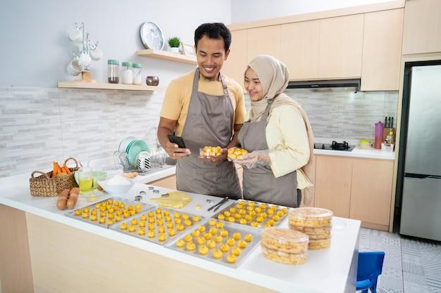 Muzułmańska para używa telefonu komórkowego do promocji swojego produktu w postaci przekąski