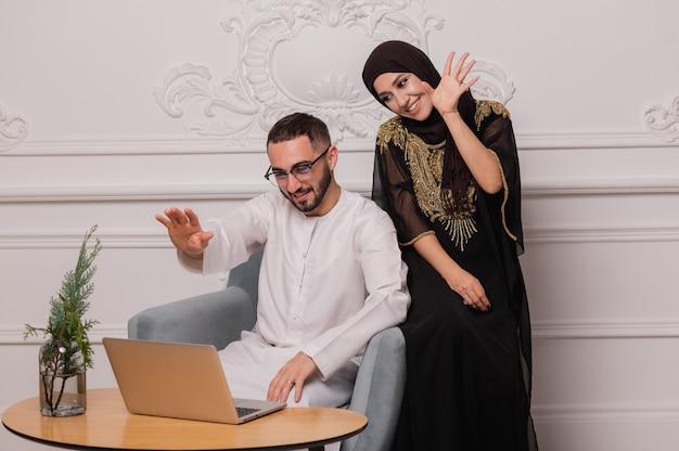 Muzułmańska para w strojach narodowych komunikuje się za pomocą komunikacji wideo. wideokonferencja z przyjaciółmi.