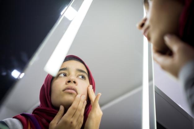 Muzułmańska piękna dziewczyna patrzeje w lustro sprawdza skóry twarz