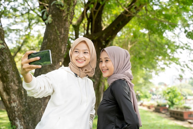 Muzułmańska przyjaciółka robi selfie lub wideorozmowy na świeżym powietrzu za pomocą smartfona podczas uprawiania sportu