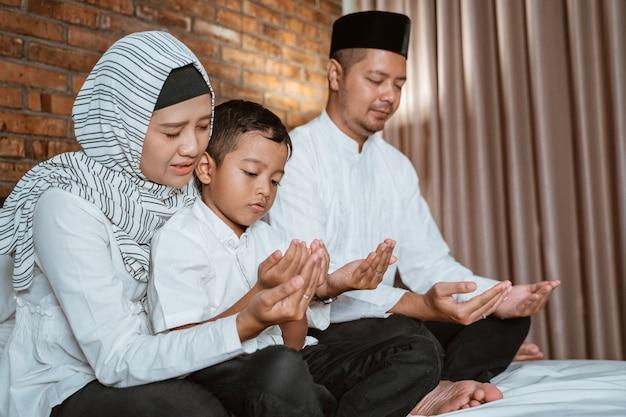 Muzułmańska rodzina modli się na łóżku